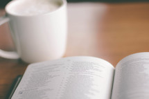 coffe cup and an open Bible