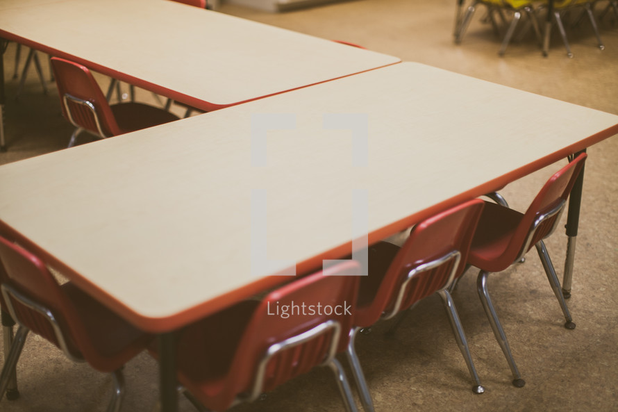 chairs under a table in a classroom