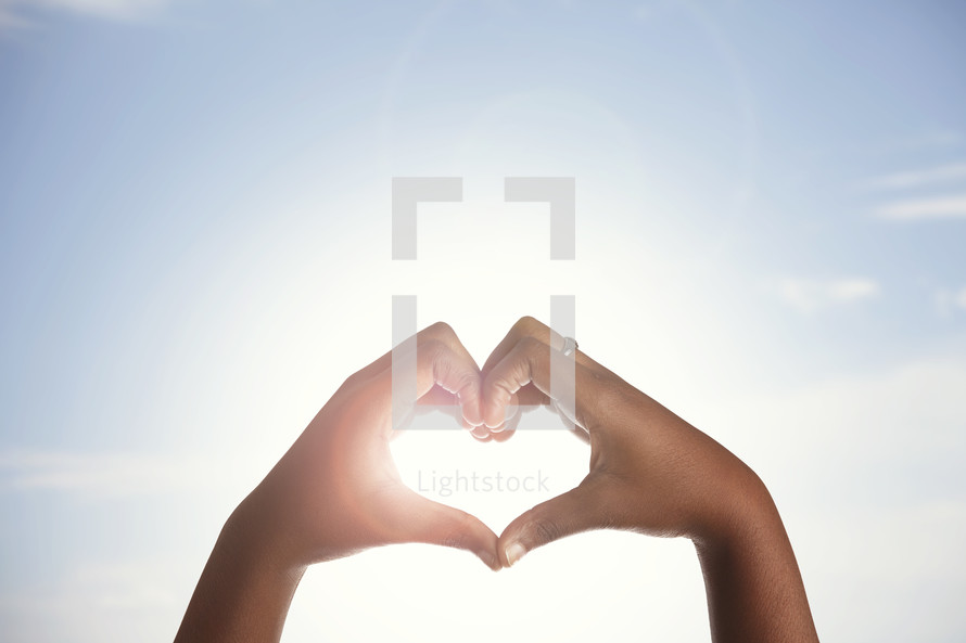 hands forming a heart shape around the sun.
