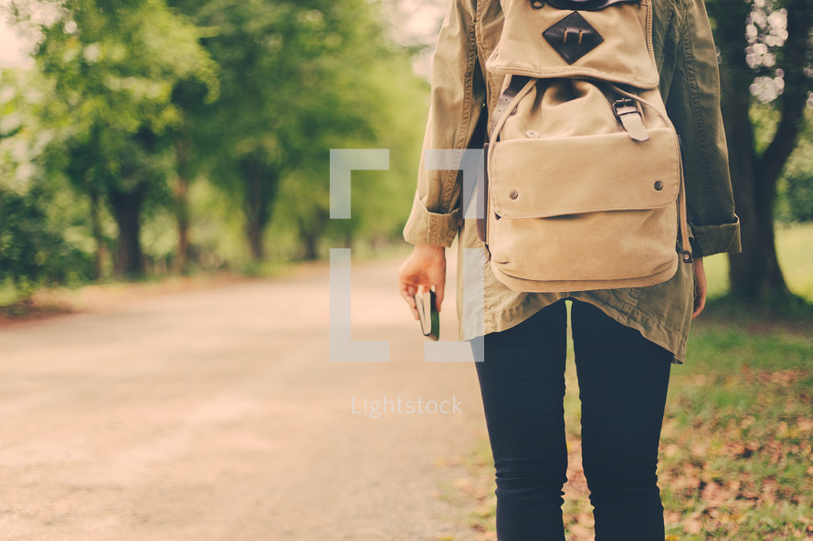 a woman with a backpack walking carrying a Bible