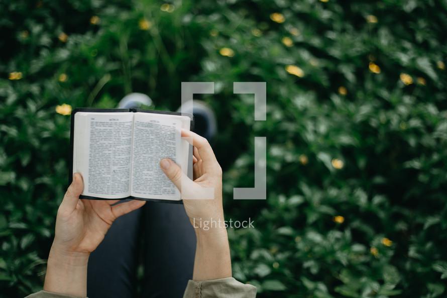 a girl reading a pocket Bible