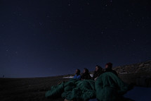 campers in sleeping bags looking up at the night sky
