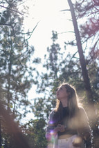 teen girl standing in a forest looking up