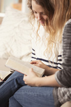 Friends sitting on the sofa together reading the Bible.