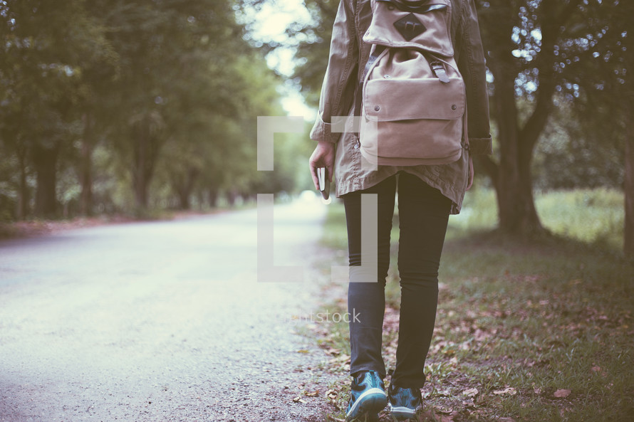 a woman walking carrying a Bible