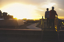 Two young men on rooftop at sunset.
