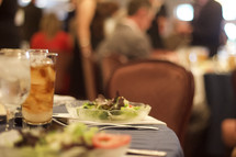 A salad plate and drink at a fundraising banquet dinner.
