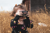 a child taking a picture with an old camera