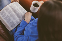 A woman siting in a chair reading her Bible and drinking coffee