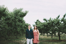 a couple in an orchard holding hands