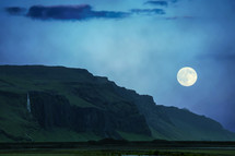 full moon over green cliffs