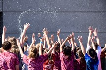 excited children being splashed with water
