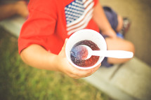 a child holding a snow cone