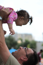 Father lifting his child in the air.