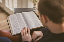 Man reading the Bible in his home with coffee.