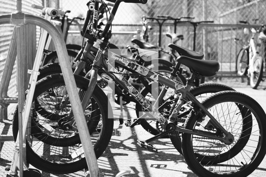 rows of parked children's bicycles on bike racks at a school