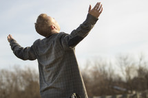 man with open arms looking up to God