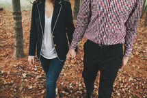 a man and woman walking outdoors in fall holding hands