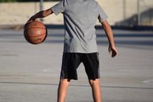 an African American boy dribbling a basketball outdoors