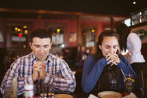 praying before a meal in a restaurant