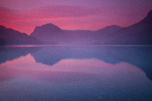 mountains reflecting on lake water under a purple sunset