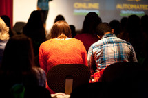 Couple in audience during a bible study presentation.