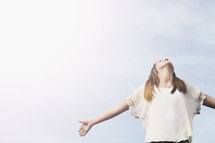 Young teenage girl with arms extended looking into the heavens.