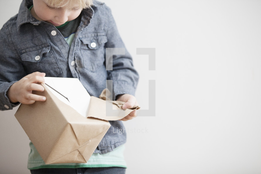 A Child opening a wrapped box.