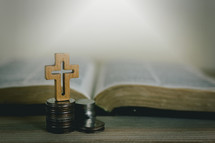 open Bible and cross on a stack of coins
