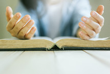 praying hands on the pages of a Bible