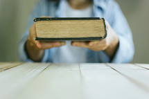 a woman holding a Bible up