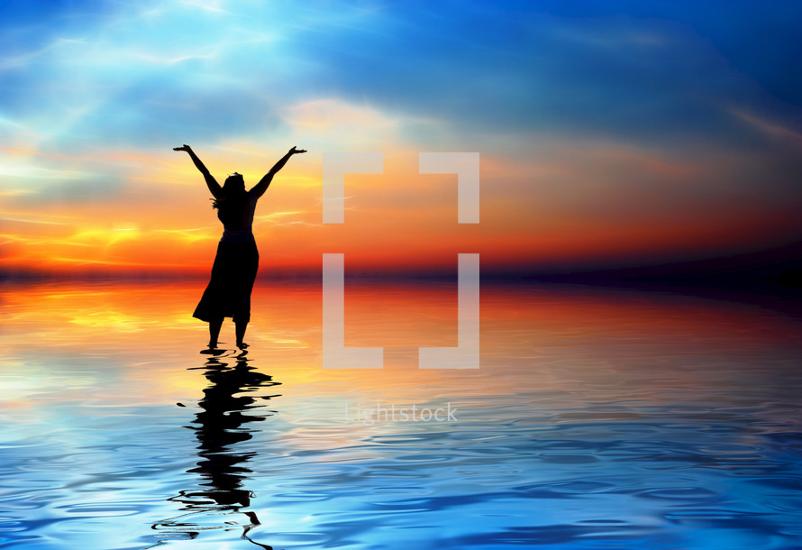 Silhouette of woman standing on water praising God.