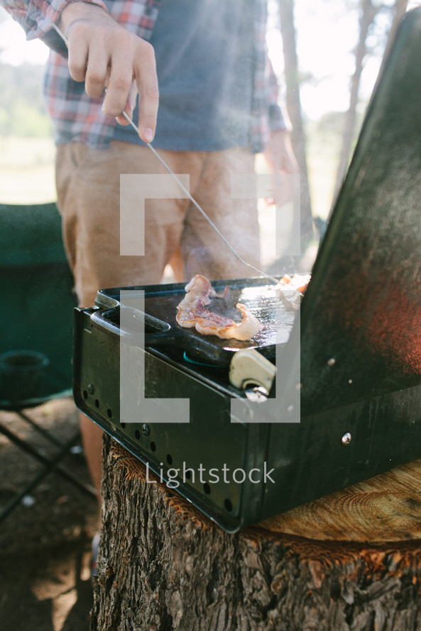 a man cooking breakfast at a camp site