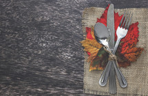 burlap placemat and silverware on fall leaves for dinner party
