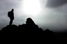 silhouette of a hiker standing on a rock under a cloudy sky