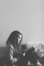 Woman sitting on a sofa reading the Bible.