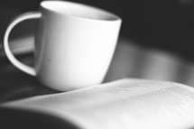 Coffee cup and open Bible on a table.