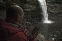 man reading a pocket Bible near a waterfall