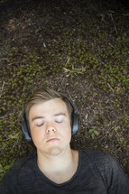 Teenager listening to music and lying down on grass and earthy background