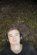 Teenager listening to music and lying down on grass and earthy background looking at camera