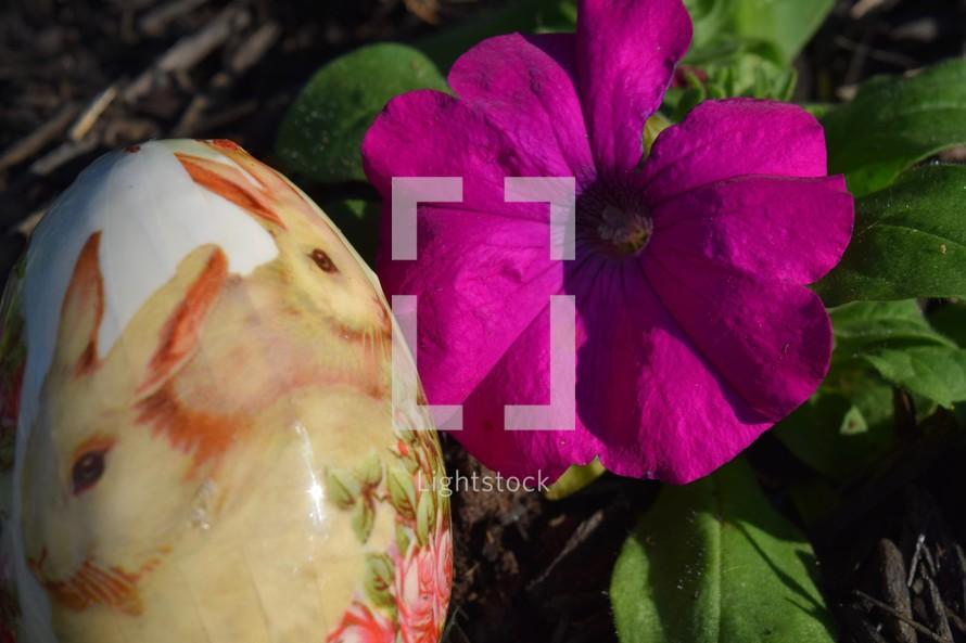 Bunnies on an Easter egg hidden next to a Petunia