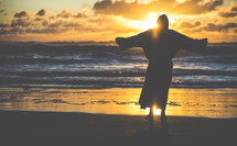 silhouette of Jesus with open arms on a shore at sunset