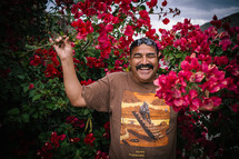 A smiling man standing among flowering bushes.