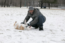 a smiling man playing in snow with a bulldog
