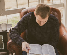 Man sitting in a chair reading the Bible.