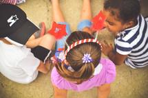 children sitting on the pavement