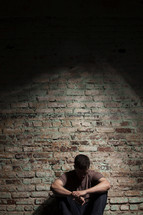 depressed man sitting against a brick wall.