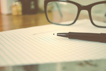 pen and reading glasses on graph paper