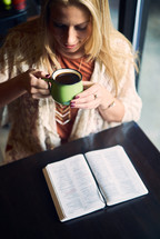 a woman reading a Bible and drinking coffee in a coffee shop