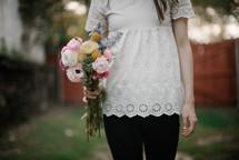 a teen girl holding a bouquet of flowers